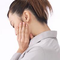 顎を抑える女性の後ろ姿